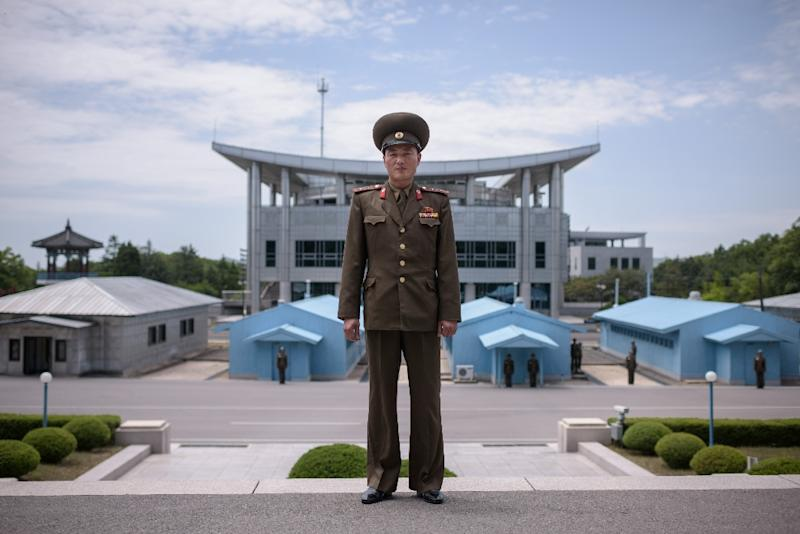A North Korean soldier stands before the military demarcation line separating the two Koreas, with 'Peace House' - where the summit will take place - in the background on the right (AFP Photo/Ed JONES)