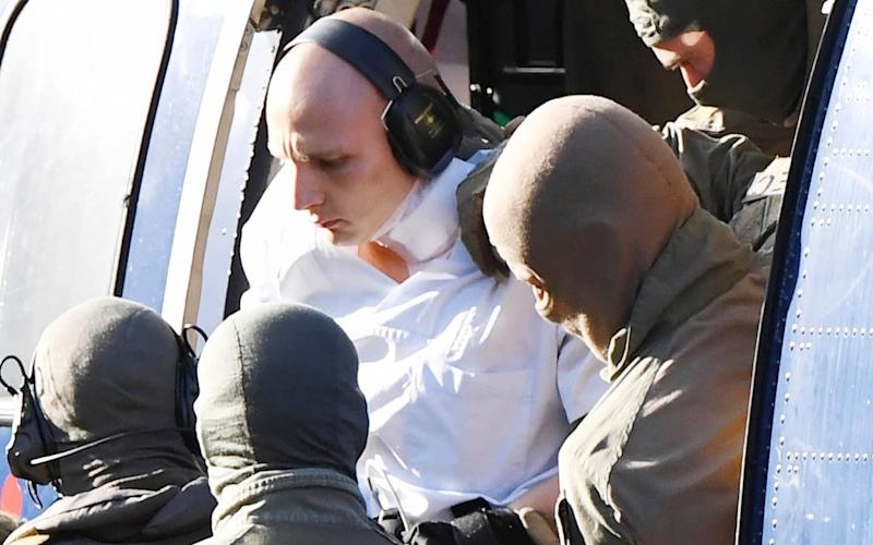Stephan Balliet in a white overall is escorted by Police officers as he arrives at the federal prosecutor's office in Karlsruhe - AP