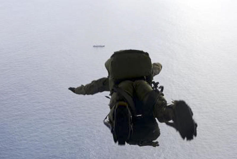 In this May 3, 2014, image provided by the U.S. Air Force, a U.S. Air Force Airman parachutes into the Pacific Ocean to aid two critically injured sailors aboard a Venezuelan fishing boat. The Venezuelan fishing boat found the sailors floating in a raft Friday afternoon after their vessel sank off the coast of Mexico, said Sarah Schwennese, spokeswoman at the Davis-Monthan Air Force Base in Tucson. (AP Photo/U.S. Air Force, Staff Sgt. Adam Grant)