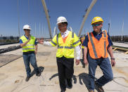 Secretary of Labor Marty Walsh, center, visits the Frederick Douglass Memorial Bridge construction site together with District of Columbia Mayor Muriel Bowser and Secretary of Transportation Pete Buttigieg, in southeast Washington, Wednesday, May 19, 2021. (AP Photo/Manuel Balce Ceneta)
