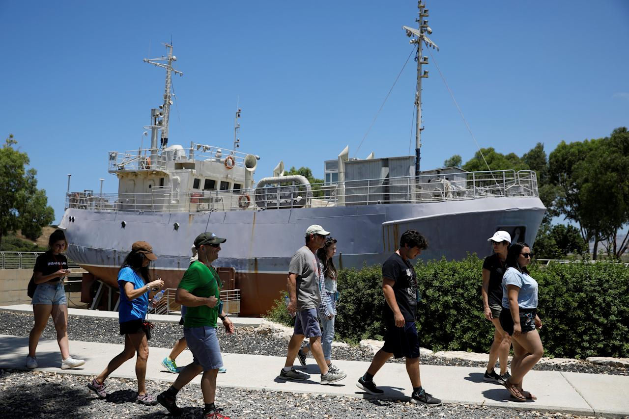 Tourists walk past an original ship used to illegally bring Jewish immigrants, at the former British detention camp of Atlit, currently operated as a museum by the Council for Conservation of Heritage Sites in Israel, June 19, 2018. Picture taken June 19, 2018. REUTERS/Amir Cohen