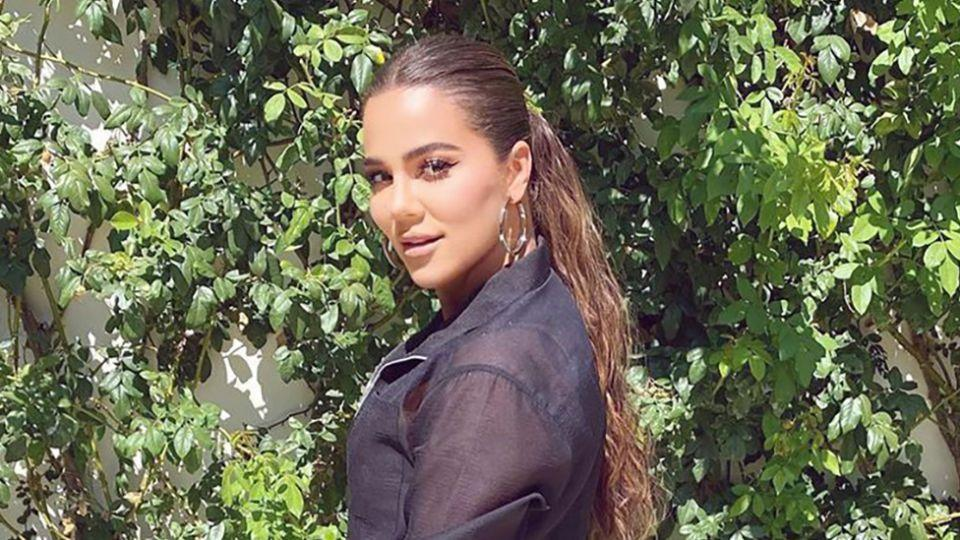 Khloe Kardashian wearing a black shirt and her hair in a ponytail