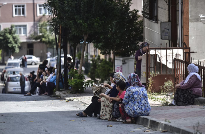 People sit and stand on the streets after evacuating their homes, following an earthquake in Istanbul, Thursday, Sept. 26, 2019. Turkey's emergency authority says a 5.8 magnitude earthquake has shaken Istanbul with no immediate damage reported. (DHA via AP)