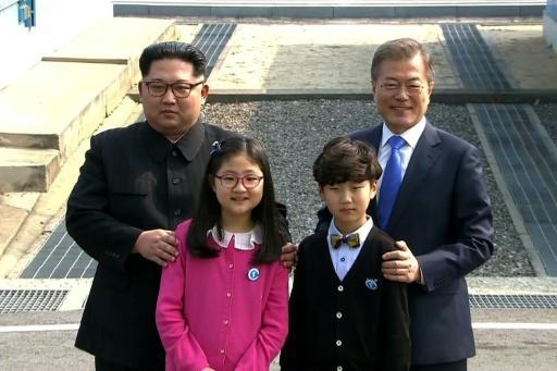 North Korea's leader Kim Jong Un and South Korea's President Moon Jae-in (R) stand with children as they meet at the Military Demarcation Line that divides their countries at Panmunjom
