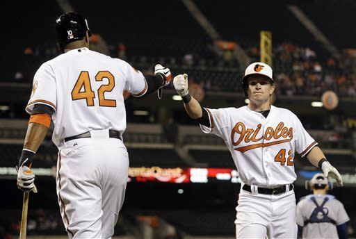 Baltimore Orioles' Nate McLouth, right, fist bumps teammate Adam Jones after scoring on a single by Nick Markakis in the third inning of a baseball game against the Tampa Bay Rays on Tuesday, April 16, 2013, in Baltimore. All uniformed members of both teams wore jerseys with No. 42 in honor of Jackie Robinson. (AP Photo/Patrick Semansky)
