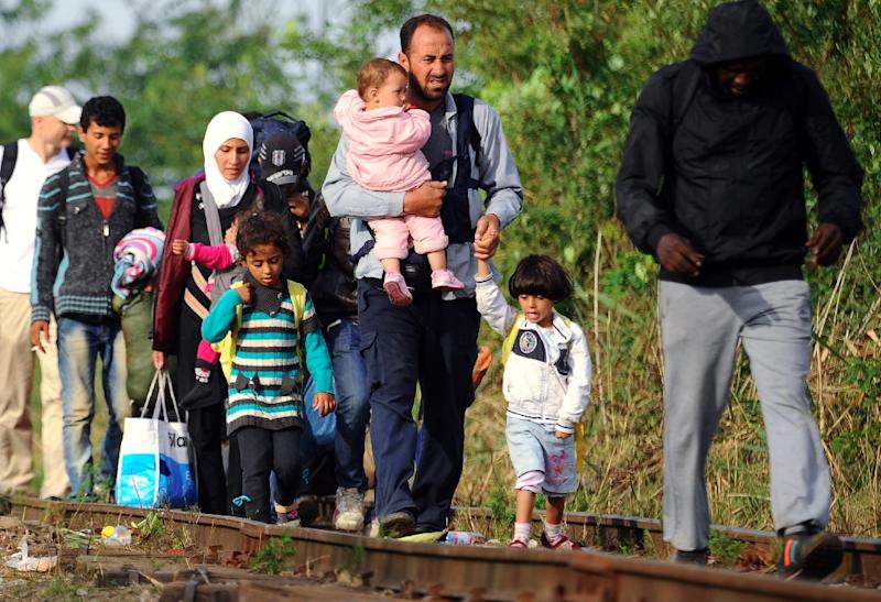 Migrant families walk along a railway track near the border village Roszke, at the Hungarian-Serbian border on August 25, 2015 (AFP Photo/Attila Kisbenedek)
