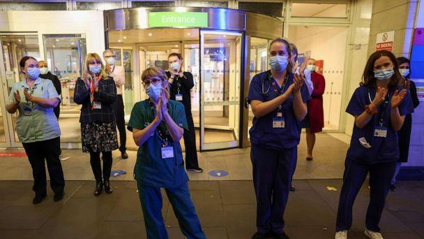 PHOTO: NHS staff participate in a national clap for late Captain Sir Tom Moore and all NHS workers, amidst the coronavirus disease (COVID-19) outbreak, at Chelsea and Westminster Hospital in London, Feb. 3, 2021. (Kevin Coombs/Reuters)