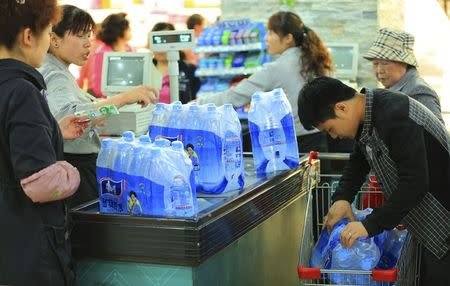 People buy bottled water at a supermarket in Lanzhou
