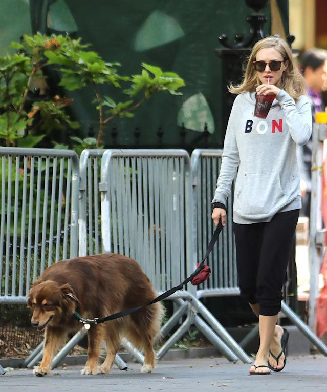 <p>The actress may have been in a sweatshirt, but walking her dog, Finn, clearly called for a cool beverage. (Photo: AKM-GSI) </p>