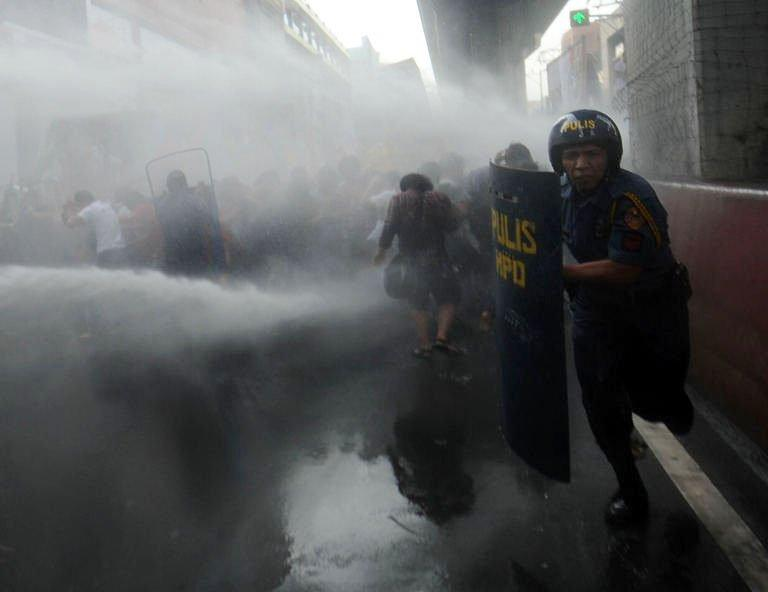 Student protesters cover themselves from a water cannon fired at them by the police