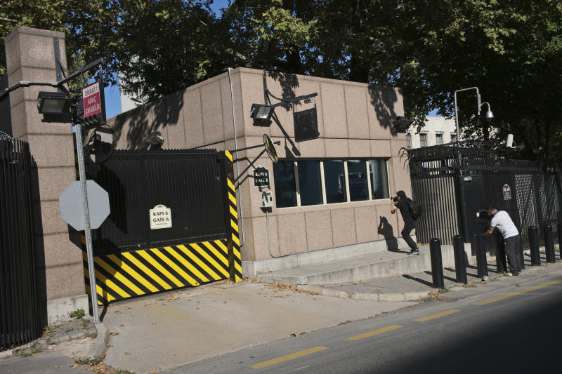 Members of the media take pictures of the damage to a security booth by a shot fired, outside the U.S. Embassy in Ankara, Turkey, Monday, Aug. 20, 2018. Shots were fired at a security booth outside the embassy in Turkey's capital early Monday, but U.S. officials said no one was hurt. Ties between Ankara and Washington have been strained over the case of an imprisoned American pastor, leading the U.S. to impose sanctions, and increased tariffs that sent the Turkish lira tumbling last week. (AP Photo/Burhan Ozbilici)