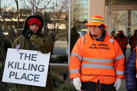 FILE PHOTO: A protester (L) and an escort who ensures women can reach the clinic stand outside the EMW Women's Surgical Center in Louisville, Kentucky, U.S. January 27, 2017.  REUTERS/Chris Kenning/File Photo