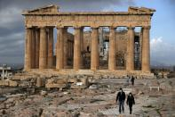 The first visitors wearing face masks to protect against the spread of coronavirus, walk atop of Acropolis hill, as the Parthenon temple is seen in the background in Athens, Monday, March 22, 2021. Greece's government reopened the Acropolis and other ancient sites nationwide after four months as it prepares to restart the tourism season in mid-May. (AP Photo/Thanassis Stavrakis)