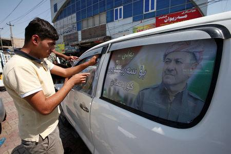 FILE PHOTO: A Kurdish man decorates a car with a poster bearing the image of Iraq's Kurdistan region's President Massoud Barzani, urging people to vote in the September 25th independence referendum, in Erbil