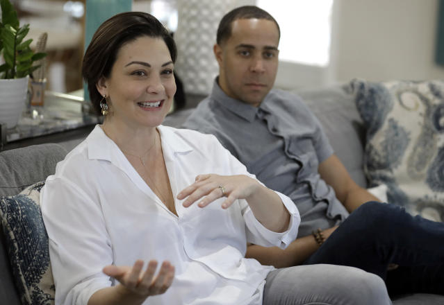 NBA referees Lauren Holtkamp-Sterling, left, gestures as she sits with her husband Jonathan Sterling, the only married couple in NBA refereeing history, during an interview at their home Thursday, Oct. 3, 2019, in Tampa, Fla. (AP Photo/Chris O'Meara)
