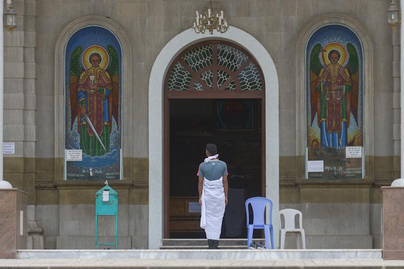 A man stands outside the entrance to a large cathedral. On either side of he door are two large mosaics depicting religious figures.