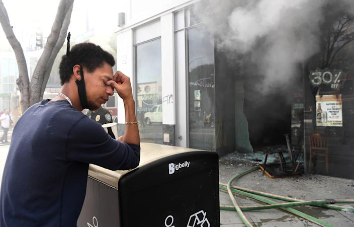 "Sake House employee, Jared Settles, can't bear to watch as the restaurant burns in Santa Monica Sunday. <span class=""copyright"">(Wally Skalij/Los Angeles Times)</span>"