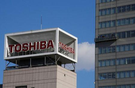 The logo of Toshiba Corp is seen as Window cleaners work on the company's headquarters in Tokyo