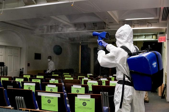 A member of the White House cleaning staff sprays the press briefing room the evening of U.S. President Donald Trump's return from Walter Reed Medical Center after contracting the coronavirus disease (COVID-19), in Washington, U.S., October 5, 2020. (Erin Scott/Reuters)