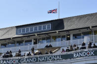 The Union Jack flies at half mast behind the stands in honour of the late Prince Philip, Duke of Edinburgh, during races on the second day of the Grand National Horse Racing meeting at Aintree racecourse, near Liverpool, England, Friday April 9, 2021. (Peter Powell/Pool via AP)