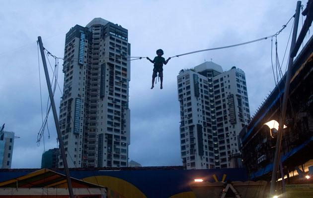 A boy plays on a giant trampoline at a mall in Mumbai July 5, 2012. REUTERS/Ahmad Masood