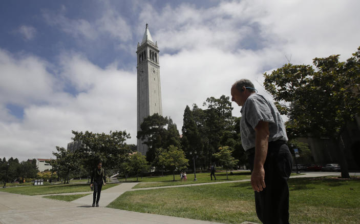 """People walk along paths on the University of California at Berkeley campus in front of Sather Tower, also known as the Campanile, in Berkeley, Calif., Thursday, July 18, 2019. Soon students in Berkeley will have to pledge to """"collegiate Greek system residences"""" instead of sororities or fraternities and city workers will have to refer to manholes as """"maintenance holes."""" Berkeley leaders voted unanimously this week to replace about 40 gender-specific words in the city code with gender-neutral terms. (AP Photo/Jeff Chiu)"""