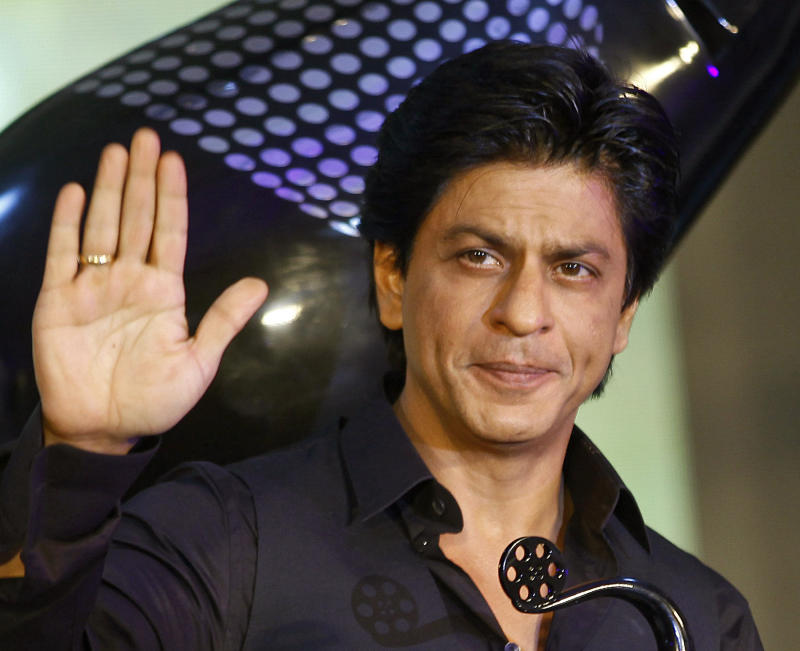 """FILE- In this Jan. 29, 2013 file photo, Bollywood actor Shah Rukh Khan waves during the unveiling of the TOIFA Bollywood awards in Mumbai, India. Veteran Indian actor and director Manoj Kumar has filed a lawsuit against Khan for releasing a popular 2007 film in Japan without deleting scenes that make fun of him. Kumar is seeking 1 billion rupees ($18.5 million) in damages from Khan and Eros International, the producers of the film, """"Om Shanti Om."""" (AP Photo/Rafiq Maqbool, File)"""