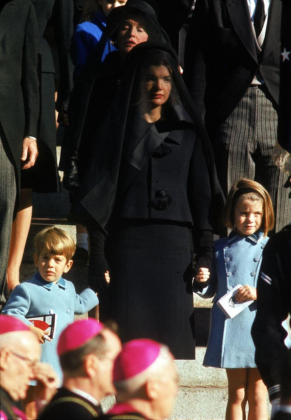<p>Jacqueline Kennedy holds the hands of her children, Caroline and JFK Jr., at the funeral of her husband, President Kennedy. </p>
