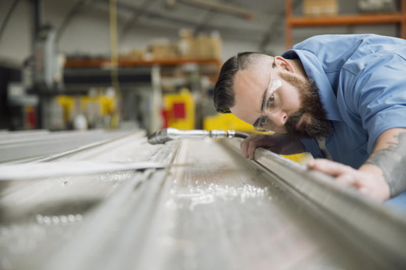 Worker examining sheet metal in manufacturing plant (GETTY)