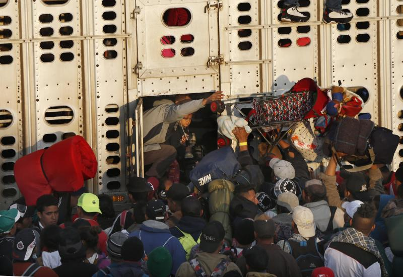 Central American migrants, part of the caravan hoping to reach the U.S. border, get a ride in a chicken truck, in Irapuato, Mexico, Monday, Nov. 12, 2018. Several thousand Central American migrants marked a month on the road Monday as they hitched rides toward the western Mexico city of Guadalajara. (AP Photo/Marco Ugarte)