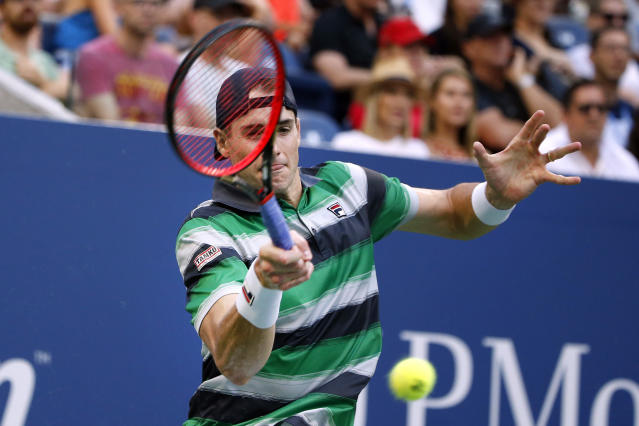 John Isner, of the United States, returns a shot to Milos Raonic, of Canada, during the fourth round of the U.S. Open tennis tournament, Sunday, Sept. 2, 2018, in New York. (AP Photo/Jason DeCrow)
