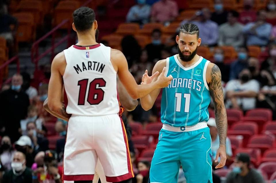 Twin brothers Miami Heat forward Caleb Martin (16) and Charlotte Hornets forward Cody Martin (11) shake hands before Monday's preseason game. The Martin Twins played together in Charlotte the past two seasons.