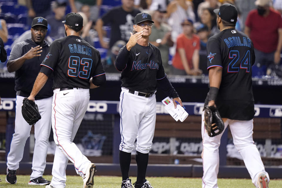 Miami Marlins manager Don Mattingly, center, greets Miami Marlins first baseman Jesus Aguilar (24) after a baseball game against the San Diego Padres, Saturday, July 24, 2021, in Miami. (AP Photo/Lynne Sladky)