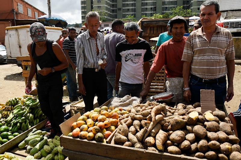 People buy groceries at the municipal market of Coche, a neighborhood in Caracas (AFP Photo/Federico PARRA)