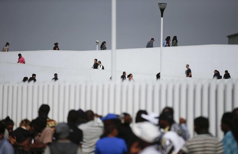 People use the legal border crossing into the United States, top, as migrants, below, wait  to apply for asylum in the U.S., on the border in Tijuana, Mexico, Sunday, June 9, 2019. The mechanism that allows the U.S. to send migrants seeking asylum back to Mexico to await resolution of their process has been running in Tijuana since January. (AP Photo/Eduardo Verdugo)