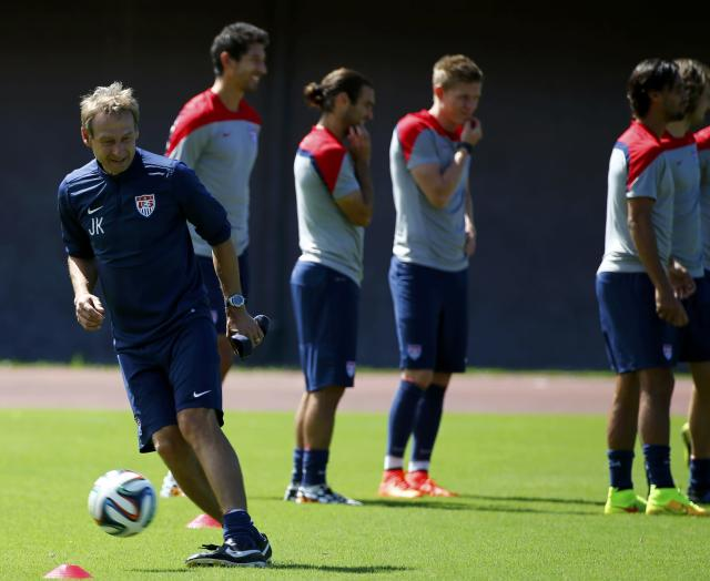 U.S. national soccer team coach Juergen Klinsmann plays a ball on the pitch next to his players during a training session in Salvador June 30, 2014. REUTERS/Michael Dalder (BRAZIL - Tags: SOCCER SPORT WORLD CUP)