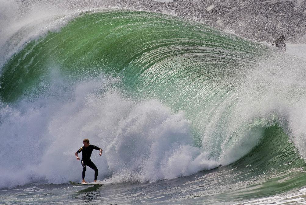 A large wave crashes behind a surfer at the Wedge in Newport Beach, Calif. on Thursday, Sept. 1, 2011. High tide and a winter storm off New Zealand are combining to bring high waves to the Southern California coast. The National Weather Service said waves of 8 feet to 11 feet or more could hit beaches from San Luis Obispo to San Diego counties through the afternoon and peak Thursday night or early Friday. (AP Photo/Orange County Register, Mark Rightmire)