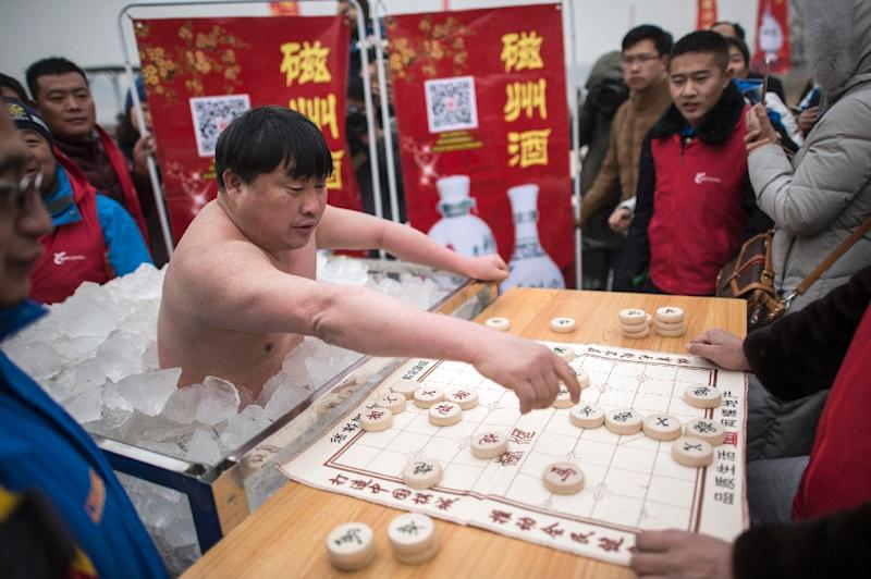 "Cui Deyi, known as ""Polar Bear,"" plays mahjong while standing waist-deep in a box filled with ice in Handan, in China's Hebei province on January 16, 2016 (AFP Photo/Fred Dufour)"