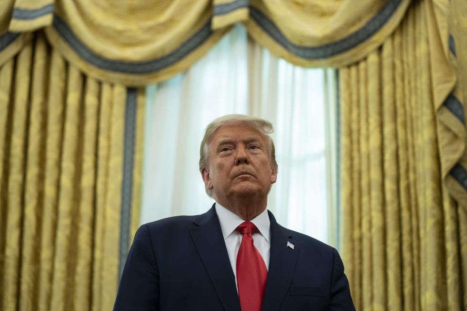 President Donald Trump listens during a ceremony to present the Presidential Medal of Freedom to former football coach Lou Holtz, in the Oval Office of the White House, Thursday, Dec. 3, 2020, in Washington. (AP Photo/Evan Vucci)
