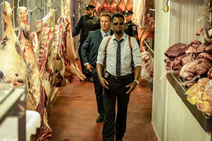 Chris Rock, followed by a man in a suit and two uniformed police officers, walk past hanging meat in a slaughterhouse.