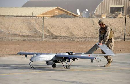 A U.S. Marine with Marine Unmanned Aerial Vehicle Squadron 1 pushes an RQ-7B Shadow UAV following its landing at Camp Leatherneck, Afghanistan in this November 10, 2011 USMC handout photo obtained by Reuters February 6, 2013.  To match Exclusive AFGHANISTAN-DRONES/       U.S. Marine Corps/Sgt. Eric D. Warren/Handout via Reuters/File Photo   ATTENTION EDITORS -  THIS IMAGE HAS BEEN SUPPLIED BY A THIRD PARTY. FOR EDITORIAL USE ONLY.