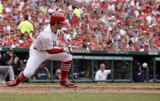 St. Louis Cardinals' Pete Kozma lays down a bunt for a squeeze play to score Jon Jay from third during the fourth inning of a baseball game against the Milwaukee Brewers, Sunday, May 19, 2013, in St. Louis. (AP Photo/Jeff Roberson)
