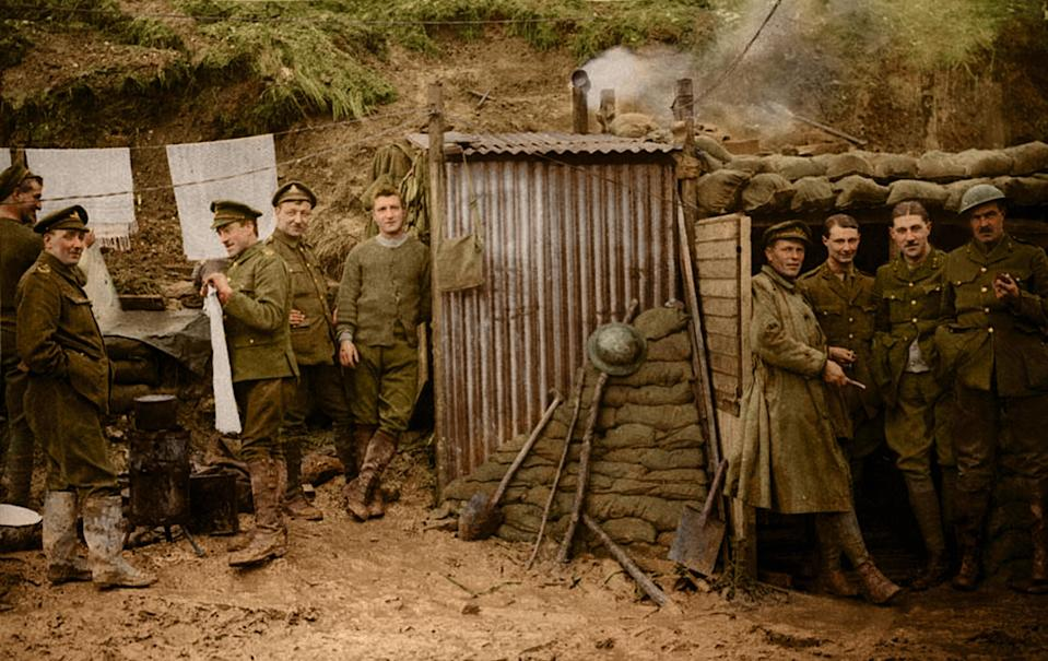 <p>This photograph shows a group of soldiers standing in the entrance to a dugout. Other men are outside, standing beside a washing line with towels on it. A pot is steaming on a brazier made of a tin drum. This rather domestic scene appears well removed from the reality of the trenches at the Front. It may have been intended to counter criticism of the campaign by implying that it was better organised than was the case. (Tom Marshall/mediadrumworld.com) </p>