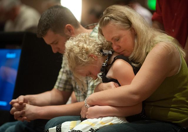 Lara Stern, right, holds her daughter, Alana, 8, and husband Samuel Stern on Sunday, June 16, 2013 during a community prayer and praise worship service at First Baptist Church near Colorado Springs, Colo. The Stern family and at least ten other families at the church lost their homes to the Black Forest wildfire. (AP Photo/The Colorado Springs Gazette, Mark Reis)