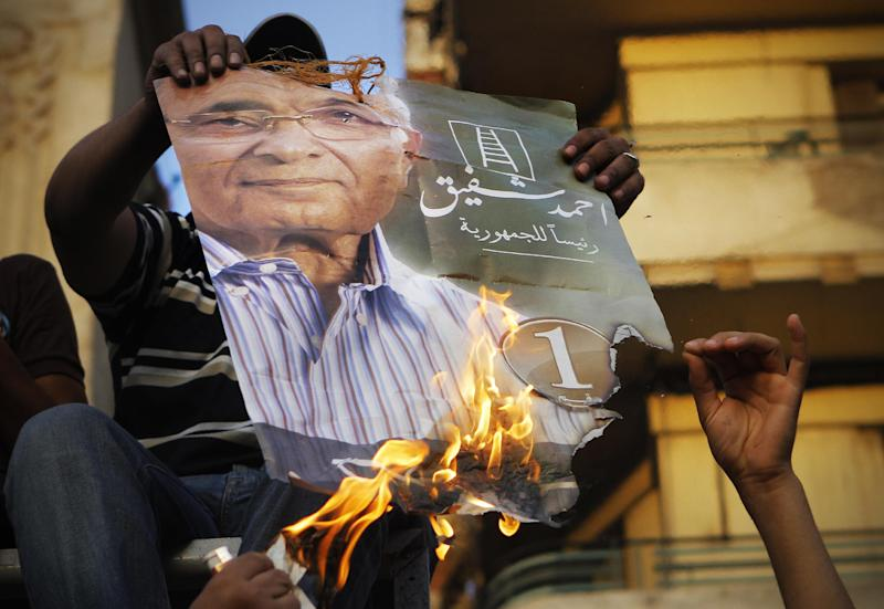 """Muslim brotherhood's presidential candidate Mohammed Morsi supporters burn a poster for presidential candidate Ahmed Shafiq, in Tahrir Square, the focal point of Egyptian uprising, in Cairo, Egypt, Tuesday, June 19, 2012. The Brotherhood has called for mass demonstrations in Cairo and elsewhere on Tuesday to protest the interim charter issued by the military as well as a court ruling last week that dissolved parliament, where the Brotherhood controlled nearly half the seats. Already, several thousand protesters have gathered in Cairo's Tahrir Square, birthplace of the uprising that toppled Mubarak 16 months ago. Arabic on the poster reads, """"Ahmed Shafiq for Egyptian presidency."""" (AP Photo/Amr Nabil)"""