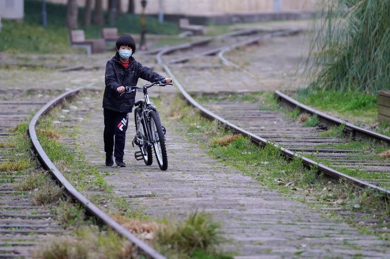 A boy wearing a face mask walks with his bicycle at a park as the country is hit by an outbreak of the novel coronavirus, in Shanghai
