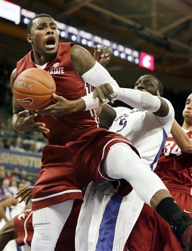 Washington State's D.J. Shelton, left, grabs a rebound over Washington's Aziz N'Diaye in the first half of an NCAA college basketball game on Sunday, March 3, 2013, in Seattle. (AP Photo/Ted S. Warren)