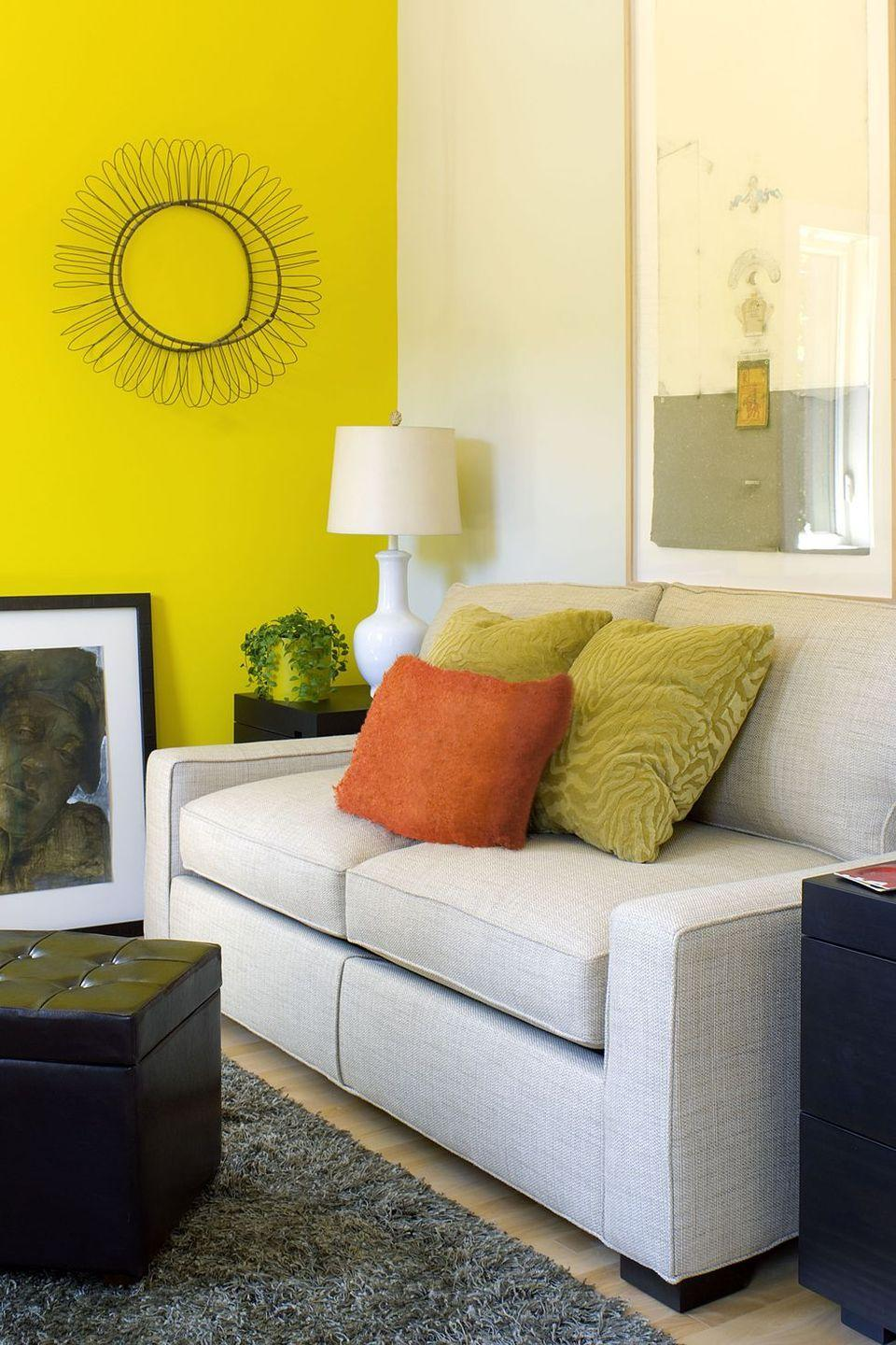 <p>Thanks to a neon yellow accent wall, this cozy living room is far from boring. </p>