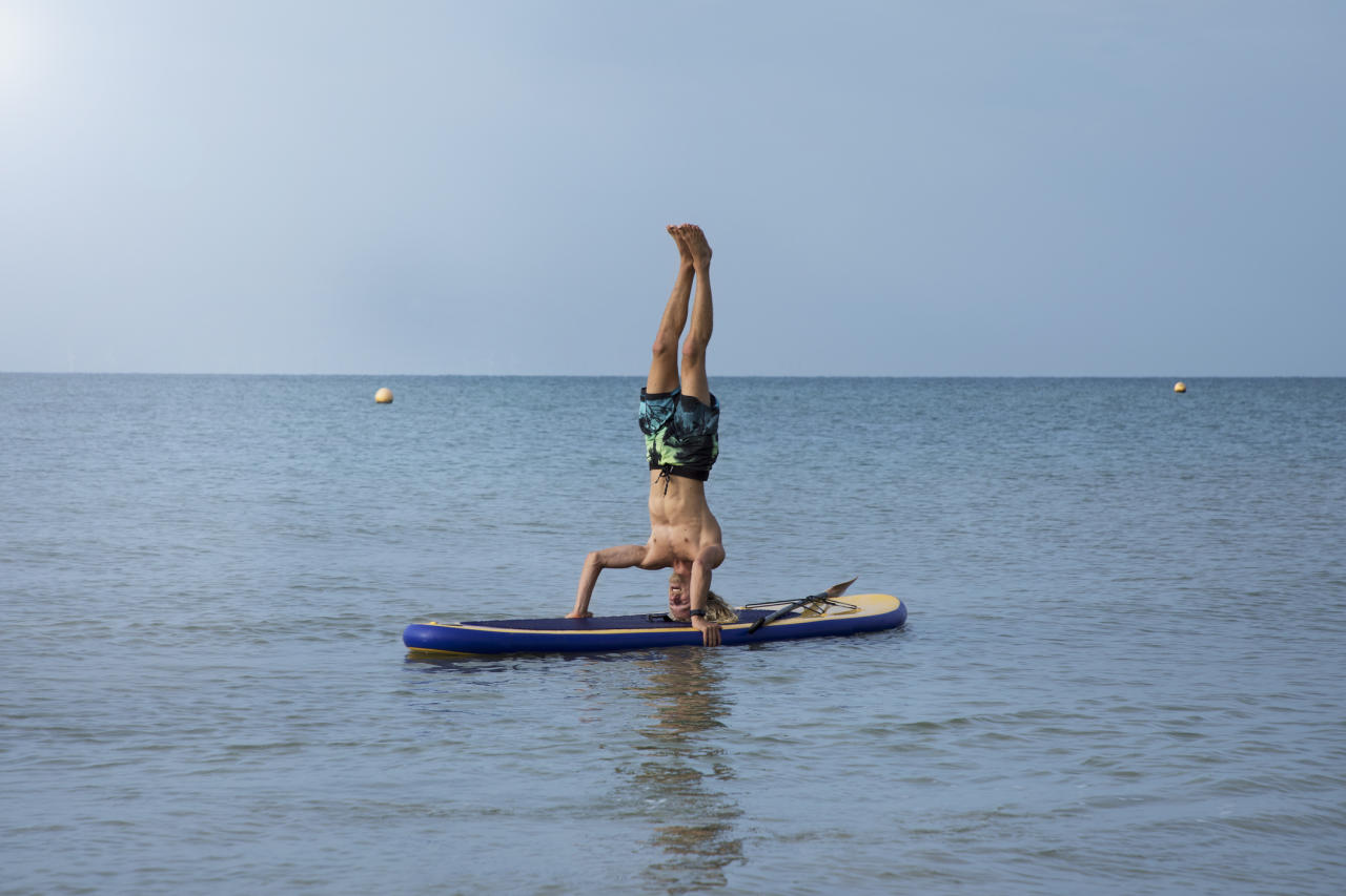 "Believe it or not, stand-up paddle boarding and yoga are the perfect partners. Your board acts like your mat and it works your core even more than regular yoga because you're balancing on water. And if you fall in? You probably wanted to cool off, right? In the calm water of Hove Lagoon, near Brighton, <a href=""https://www.lagoon.co.uk/"">Lagoon Watersports</a> offers all kinds of outdoor activities, including SUP Yoga lessons. Tethered to a buoy, you'll practice everything from downward-facing dog to seated twists while balancing on your board. Travel time: 1 hour (train from Victoria to Hove) <em>[Photo: Getty]</em>"