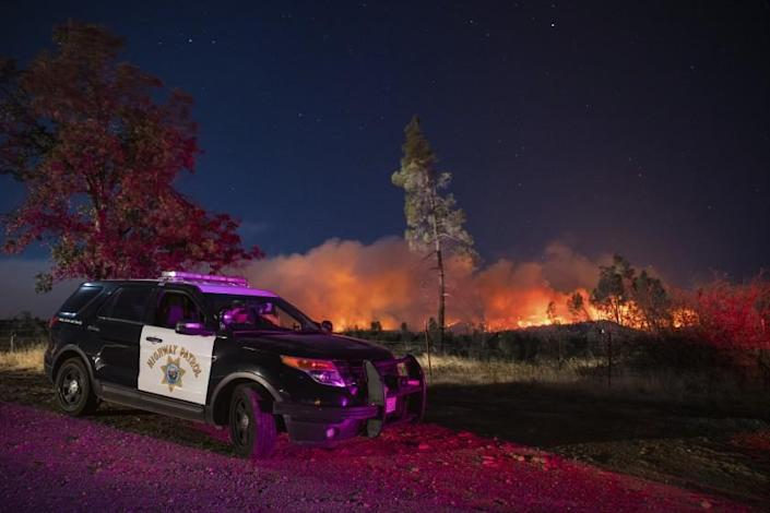 A California Highway Patrol officer watches flames that are visible from the Zogg Fire on Clear Creek Road near Igo, Calif., on Monday, Sep. 28, 2020. (AP Photo/Ethan Swope)